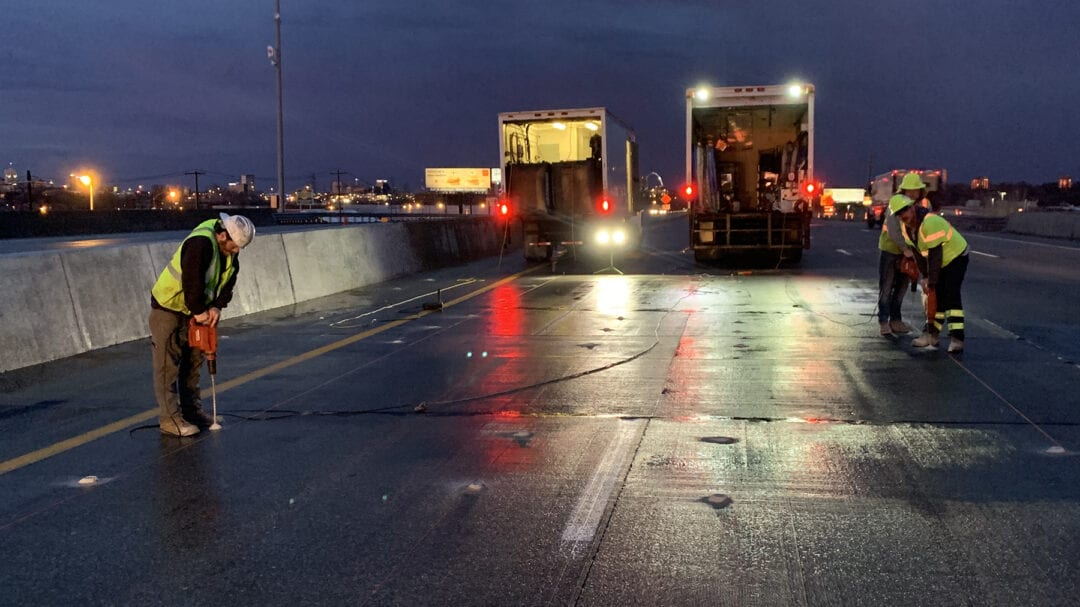 men working on road at night with truck lights glowing in the background