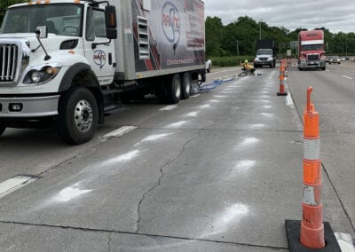 Team injecting foam under road with Raising Solutions truck in foreground