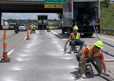 Team injecting foam under highway on a sunny day