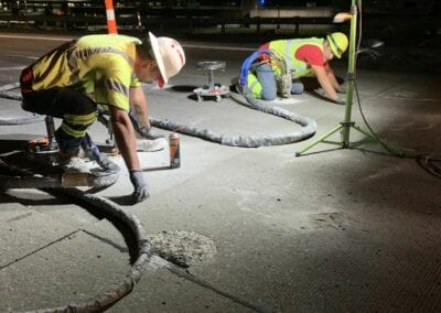 men injecting foam under road at night with work lights overhead