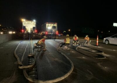 men injecting foam under road at night with truck lights glowing in the background